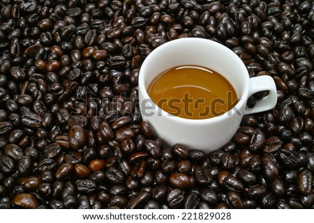 A cup of coffee milk arranged with raw coffee bean - stock photo