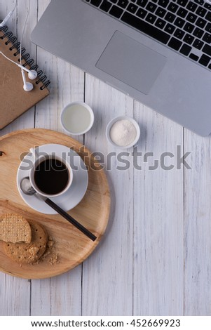 A cup of coffee on a white wooden with laptop behind it. Morning work with coffee concept.