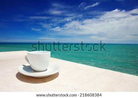 A cup of coffee on table with sea at the background - stock photo
