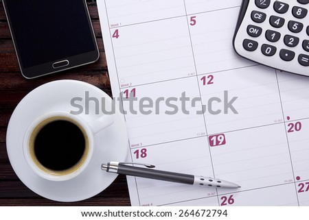 A cup of coffee on the office calendar. - stock photo