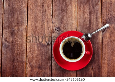 A cup of coffee on the table. Red cup and saucer. Weekday office worker. Cheer with a cup of strong coffee. Space for lettering. - stock photo