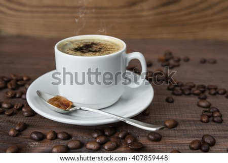 A cup of coffee on the wooden background with coffee beans