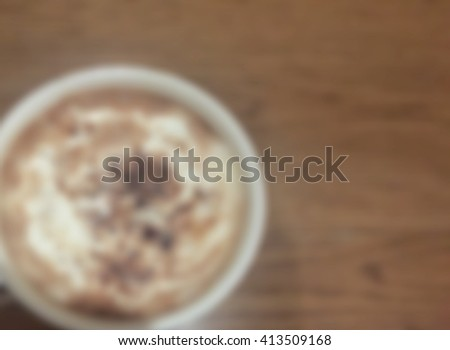 A cup of coffee on the wooden table - Blur for background