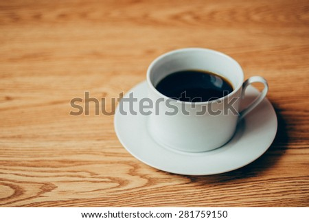 a cup of coffee on wooden background, selected focus on coffee cup.
