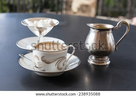 A cup of coffee, silver creamer and sugar bowl on the table on open veranda - stock photo