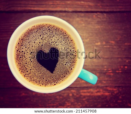 a cup of coffee with a heart shape toned with a retro vintage instagram filter  - stock photo
