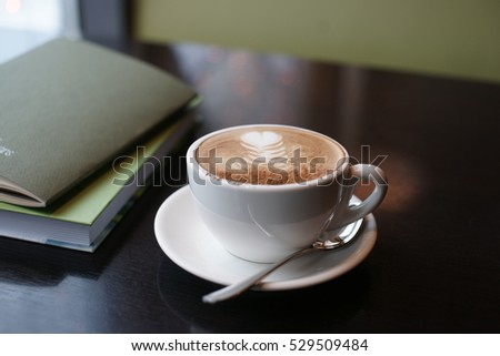 A cup of coffee with a notepad on the table.