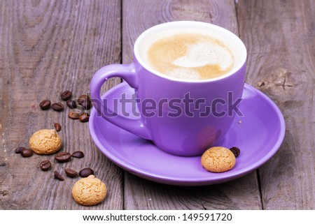 A cup of coffee with amaretti and coffee beans over wooden background