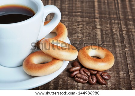 A cup of coffee with baked bagels, close-up. Coffee beans on the wooden background. - stock photo