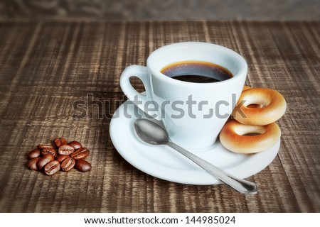 A cup of coffee with baked cracknels, bagels. Coffee beans on the wooden background. - stock photo