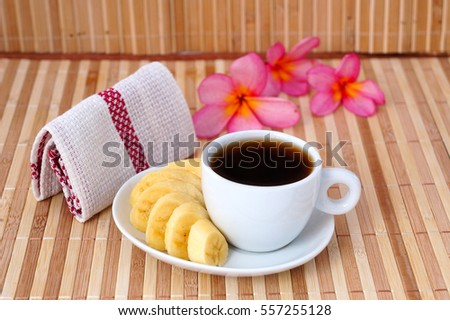 A cup of coffee with banana and handkerchief.