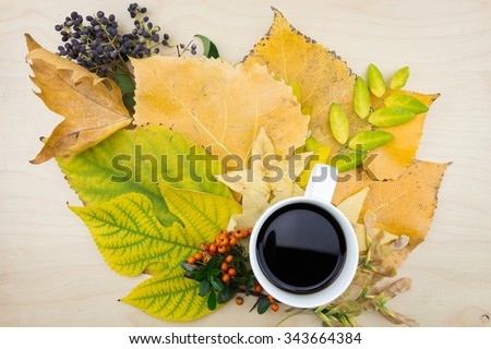 A cup of coffee with bouquet of yellow, green autumn leaves,berries and seeds. - stock photo
