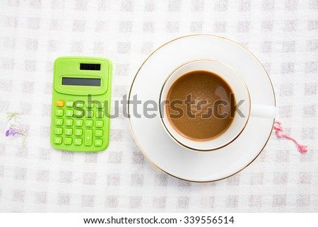 A cup of coffee with calculator