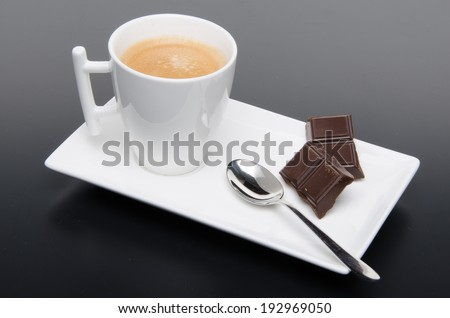 A cup of coffee with chocolate on a black background