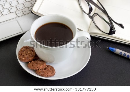 A cup of coffee with cookies, laptop, an open book and glasses on a desk. - stock photo