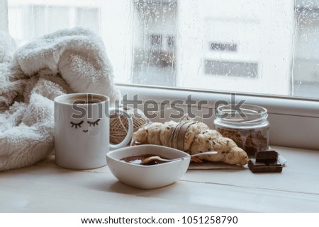 A cup of coffee with croissant,  pieces of chocolate and a thin rope beneath the window while the rain falls.