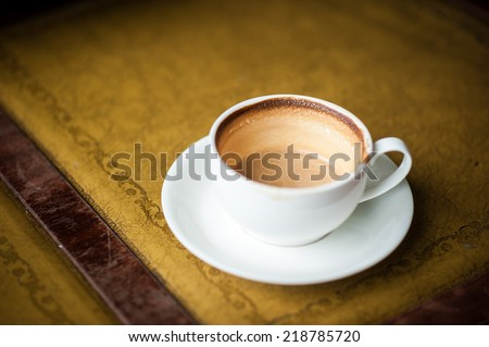 A cup of coffee with flower pattern in a white cup on vintage leather background
