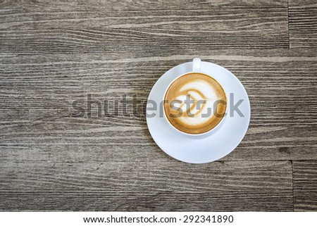 A cup of coffee with heart pattern in a white cup on wooden background - stock photo