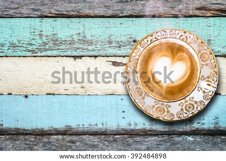 A cup of coffee with heart pattern on vintage wood table - stock photo