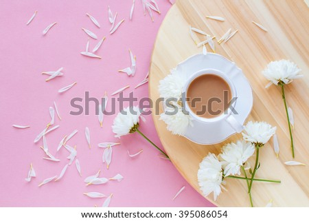 A cup of coffee with milk on a wooden board , spring flowers on a pink background top view - stock photo