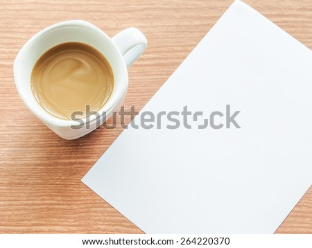 A cup of coffee with paper note on wooden table - stock photo