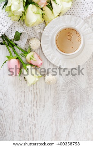A cup of coffee with roses on the wooden background