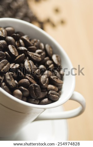 A cup of coffee with various coffee grains inside, coffee grains close up