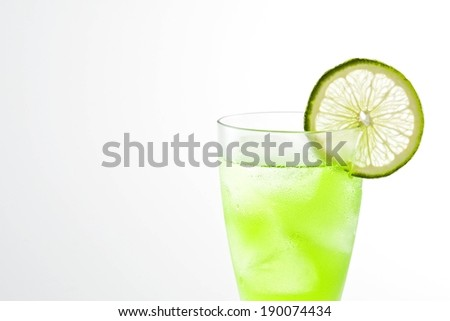 A cup of cold lime green drink and a lime slice. - stock photo