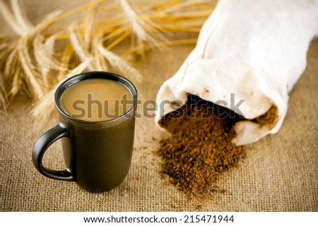 A cup of decaffeinated coffee with milk and  ears of rye at canvas - stock photo