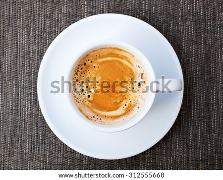 A cup of Espresso coffee on a table, top view, dark background.
