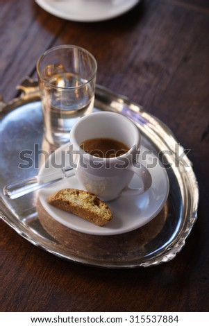 A cup of espresso with cantuccini and a glass of water - stock photo
