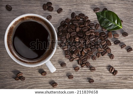 a cup of fragrant hot coffee on a wooden table with coffee beans - stock photo