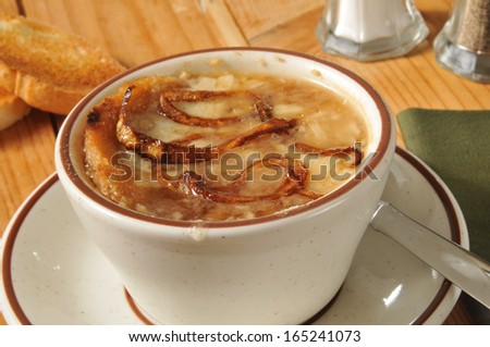 A cup of French Onion Soup on a rustic wooden table