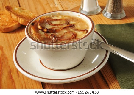 A cup of French Onion soup with toast and gruyere cheese