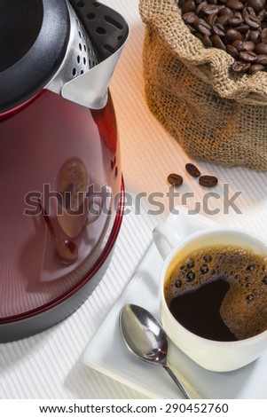 A cup of fresh coffee with a reflection on the side of a kettle - stock photo