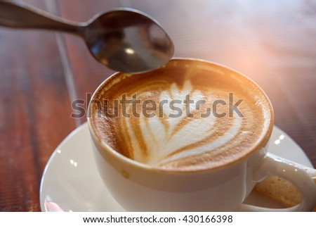 A cup of fresh hot coffee on white plate and spoon on wooden background with abstract light,selective focus - stock photo