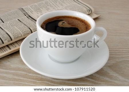 A cup of freshly brewed coffee on the table with newspaper - stock photo