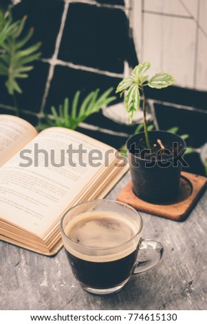 a cup of freshly coffee on a table with book