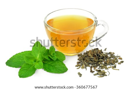 A cup of green tea and a sprig of mint and a handful of uncooked dry green tea isolated on white background.