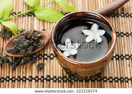a cup of green tea on bamboo mat - stock photo
