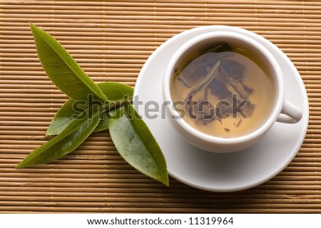 a cup of green tea with fresh leaves on the bamboo tray - stock photo