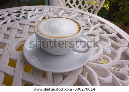 A cup of hot cappuccino coffee on the white table - stock photo