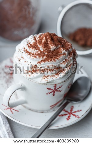 A cup of hot chocolate with whipped cream and cocoa powder - stock photo