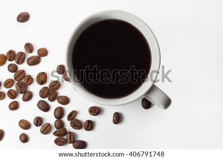 A cup of hot coffee among coffee grains. View from above.