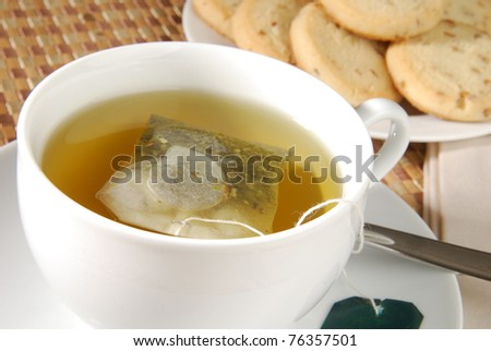 A cup of hot green tea with cookies