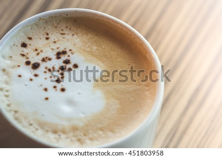 a cup of hot latte,coffee art  on the wooden table in relax time warm tone  - stock photo