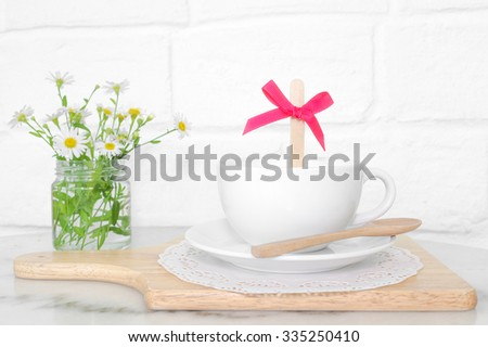 A Cup of Hot Milk with Sugar Stick in the cup, Sweet and Valentine's concept, Selective Focus on the pink bow ribbon, toned photo  - stock photo