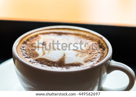 A cup of hot mocha coffee with flower pattern in a white cup