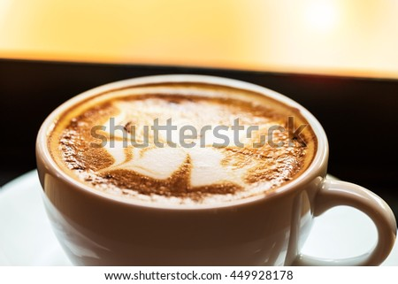 A cup of hot mocha coffee with flower pattern in a white cup at sunset time