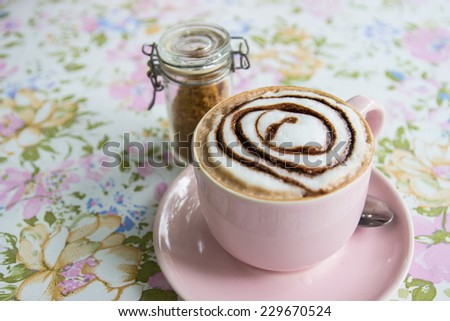 a cup of hot mocha topping with foamy milk and chocolate sauce with brown sugar - stock photo